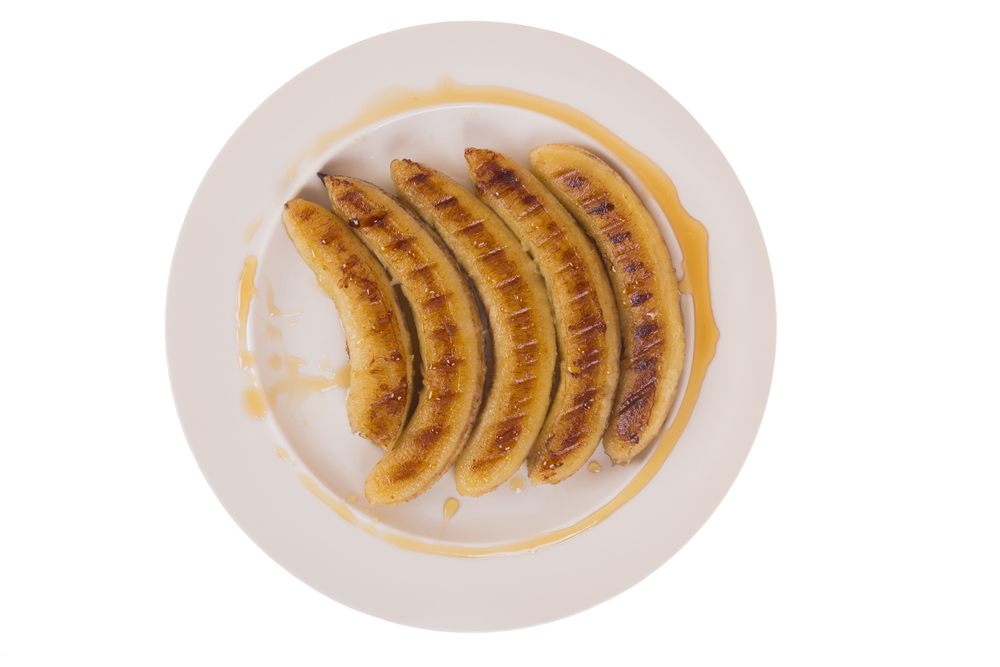 fried bananas with honey on a plate on the isolated background