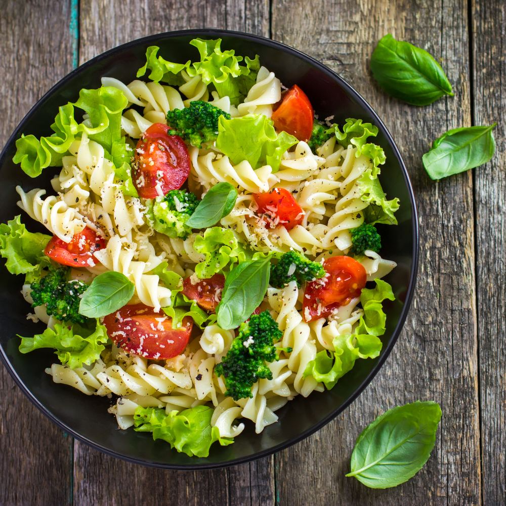 Pasta salad with cherry tomatoes and broccoli, top view, square image