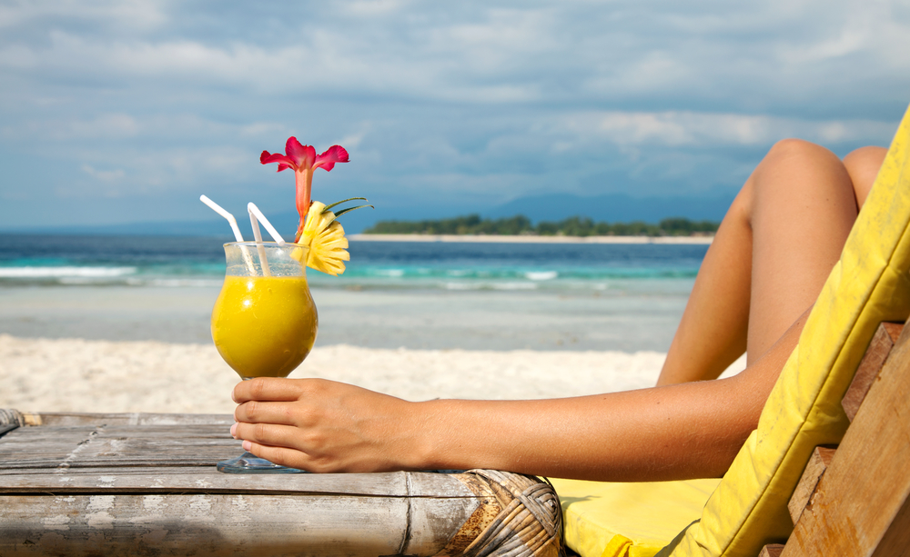 Woman holding a fruit cocktail on a tropical beach